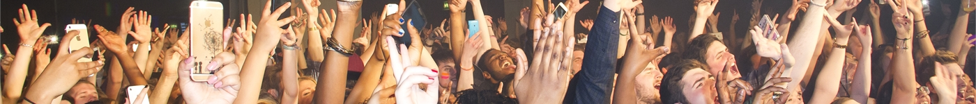 Keele students enjoying one of the many gigs in KeeleSU's Ballroom. They have their hands up as they're singing along.